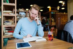 Young handsome student learning in coffee shop Stock Image