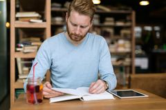 Young handsome student learning in coffee shop Stock Images