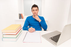Young handsome student looking at books. Royalty Free Stock Image