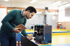 Young student of mechatronics working on project. Young handsome student of mechatronics working on project Stock Images
