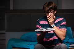 The young handsome student preparing for exams at night stock photo