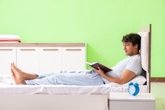 The young handsome student reading book in the bed. Young handsome student reading book in the bed royalty free stock images