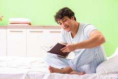 The young handsome student reading book in the bed. Young handsome student reading book in the bed royalty free stock photo