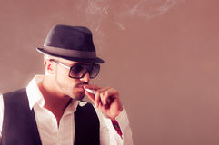 Young handsome stylish male model smoking a Stock Photos