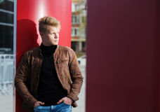 Young handsome stylish man in brown jacket in autumn time outdoor in casual style Royalty Free Stock Images