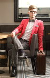 Young handsome stylish man with suitcase waits Stock Photo
