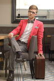 Young handsome stylish man with suitcase waits Royalty Free Stock Image
