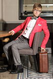 Young handsome stylish man with suitcase waits Royalty Free Stock Photo