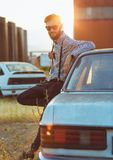 Young handsome stylish man, wearing shirt and bow-tie with old cars Royalty Free Stock Photo