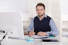 Young handsome successful accountant at desk at office. Royalty Free Stock Photo