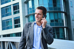 Young handsome, successful businessman, manager talking on the phone in the city, in front of modern building Stock Images