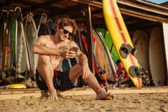 Young handsome surfer sitting and using smartphone outdoors. Young handsome surfer man in eyeglasses sitting and using smartphone outdoors Royalty Free Stock Photos