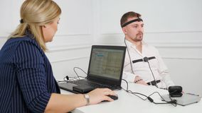 Man on Polygraph Test. Young Handsome Suspect During Interrogation Undergoes Lie Detector Connected to the Machine He Answers Yer or No royalty free stock photo