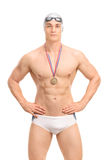Young handsome swimming champion. Vertical shot of a young handsome swimming champion in white swim trunks isolated on white background royalty free stock photos