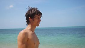 Young handsome tan man standing on the beach enjoying sunny day on vacation time , slow motion. 1920x1080 stock footage