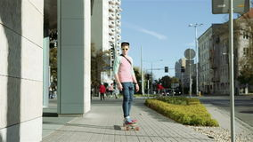 Young handsome teenager on a skateboard, outdoors. stock footage