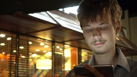 Young handsome teenager using smartphone in the night city.  royalty free stock images