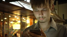 Young handsome teenager using smartphone in the night city.  royalty free stock photos
