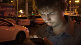 Young handsome teenager using smartphone in the night city.  stock images