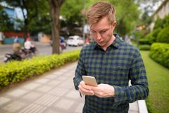Young handsome tourist man using mobile phone in Vietnam. Portrait of young handsome tourist man exploring Ho Chi Minh city in Vietnam royalty free stock photography