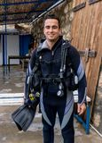 Portrait of a young handsome man diver ready to go scuba diving with cold water wet suit, fins, buoyancy compensator. Young handsome turkish latin man ready to stock images