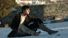 Young handsome ukrainian man in ethnic clothes sitting on the ground. Winter time stock video