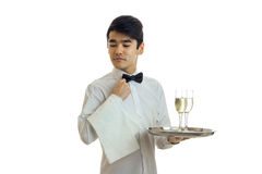Young handsome waiter with black hair lowered his eyes down and holding a towel and tray with glasses Stock Image