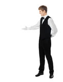 Young handsome waiter doing a welcome gesture. Isolated on white background with copy space Royalty Free Stock Photo