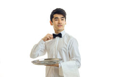 Young handsome waiter holding a tray, and adjusts his bow. Isolated on white background Stock Photography