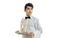 Young handsome waiter holding a tray with glasses of champagne and looks toward. On white background Stock Photos