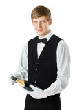 Young handsome waiter opening bottle of champagne. Portrait of young handsome waiter opening bottle of champagne isolated on white background Royalty Free Stock Images