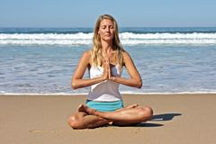 Young handsome woman meditating on the beach Royalty Free Stock Images