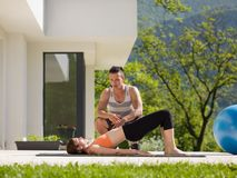 Woman with personal trainer doing morning yoga exercises. Young handsome women with personal trainer doing morning yoga exercises in front of her luxury home Stock Photography