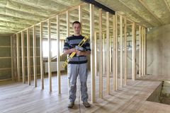 Young handsome worker with level and screwdriver looking in camera in big light attic room with oak floor, insulated ceiling and w royalty free stock photo