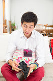 Young handsome worried man holding Christmas Royalty Free Stock Photography