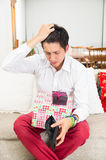 Young handsome worried man holding Christmas Stock Photos