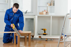 Young handyman cutting a wooden board Royalty Free Stock Images