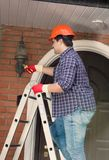 Young handyman in hardhat standing on metal stepladder and repairing lamp on th eouter wall of house. Handyman in hardhat standing on metal stepladder and Stock Image