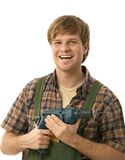 Young handyman holding power drill. Smiling. Isolated on white Royalty Free Stock Photography