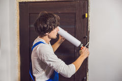 Young Handyman Installing Door With An Mounting Foam In A Room Royalty Free Stock Images