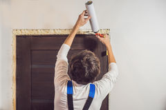 Young Handyman Installing Door With An Mounting Foam In A Room Stock Photos