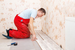 Young handyman installing wooden floor Royalty Free Stock Photo
