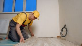 Young handyman installing wooden floor in new house. Worker puts the board flooring. Home repair concept royalty free stock image
