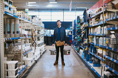 Young handyman posing in a hardware store. Standing smiling at the camera in the aisle between racks of merchandise Stock Photography
