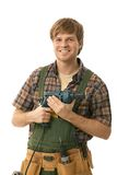 Young handyman with power drill. Young handyman holding power drill, smiling. Isolated on white Stock Image