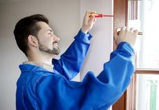 Young handyman repair window with screwdriver.  royalty free stock images