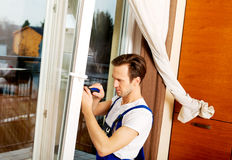 Young handyman repair window with screwdriver Royalty Free Stock Photos
