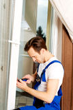 Young handyman repair window with screwdriver Stock Image