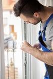 Young handyman repair window Stock Photo