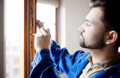 Young handyman repair window with screwdriver.  stock images